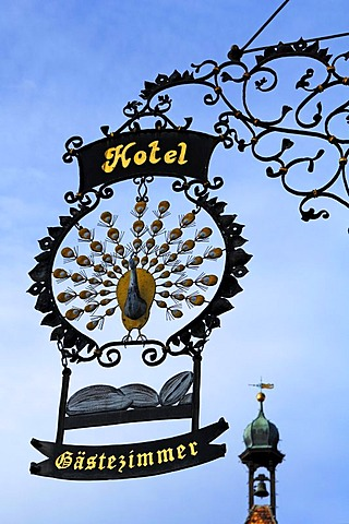 "Elaborate advertising sign ""Hotel Pfauen"" hotel peacock, in the back an old gate tower, Hauptstr. 78, Endingen am Kaiserstuhl, Baden-Wuerttemberg, Germany, Europe"