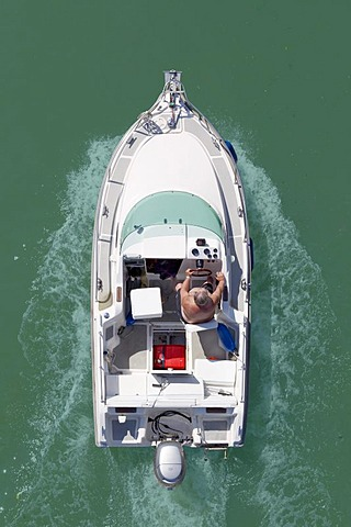 Man steering a motor boat, from above