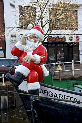 """Santa Claus figure on the bow of the historic ship """"Margaret"""" in the Fleth canal in Buxtehude, Lower Saxony, Germany, Europe"""