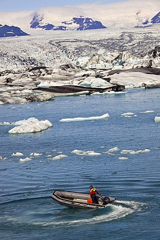 Inflatable boat on Joekulsarlon glacial lake, icebergs with different colours due to the black from volcanic ash, Joekulsarlon, Vatnajoekull, Iceland, Europe