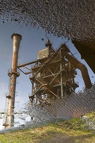 Blast furnace reflected in a puddle, Landschaftspark Duisburg Nord landscape park, Ruhrgebiet area, North Rhine-Westphalia, Germany, Europe