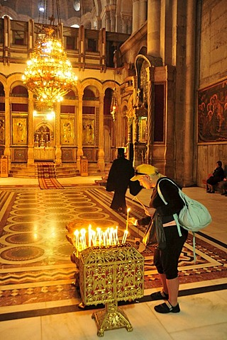 Christian pilgrim lights candle, Church of the Holy Sepulchre, Jerusalem, Israel, Middle East, Orient