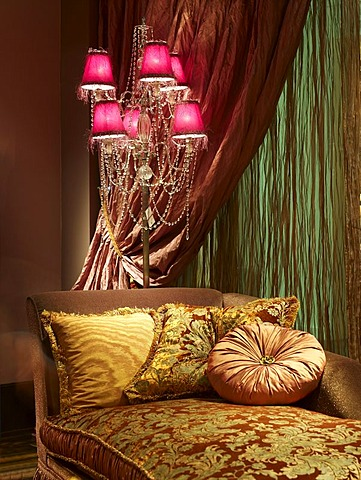 Baroque canape in luxurious surroundings with atmospheric lighting and draped curtain fabrics