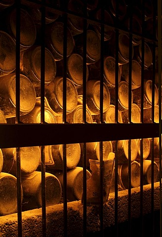 Dusty, wine bottles in storage in an old wine cellar behind iron bars