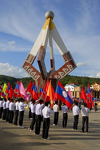 Festival, young men of the Lao Youth Organization carrying colourful flags in front of a monument, Xam Neua, Houaphan province, Laos, Southeast Asia, Asia