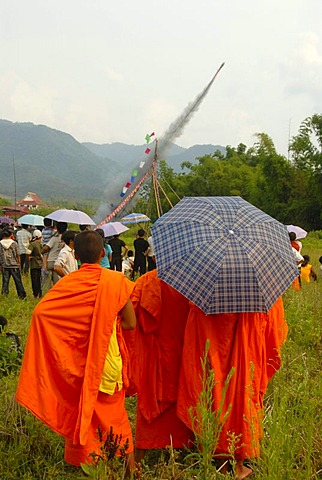 Festival, launching of a Bang Fai rocket, being watched by monks dressed in orange robes, Muang Xai, Oudomxai province, Laos, Southeast Asia, Asia