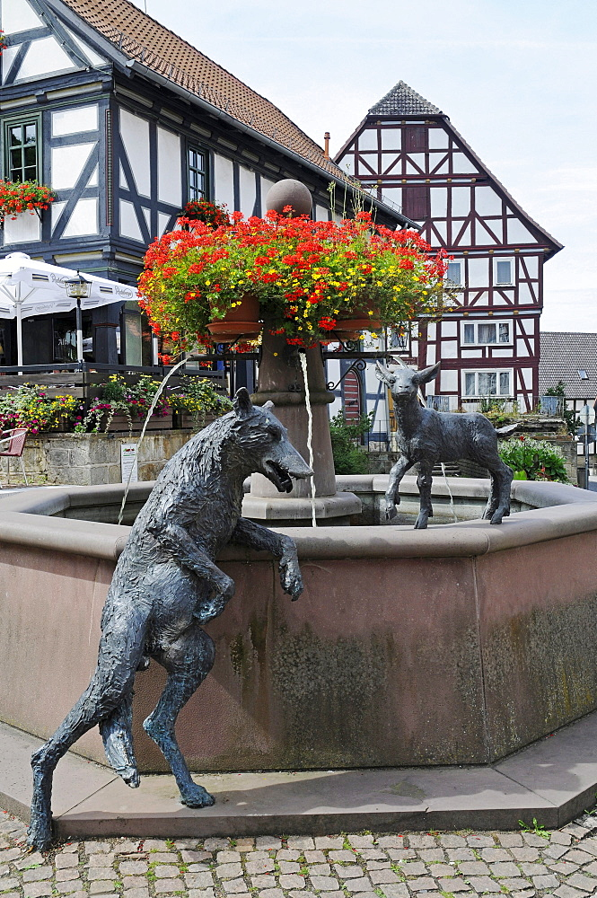 Fountain with sculptures of a wolf and a lamb on the market square with half-timbered houses, Wolfhagen, Habichtswald National Park, Hesse, Germany, Europe
