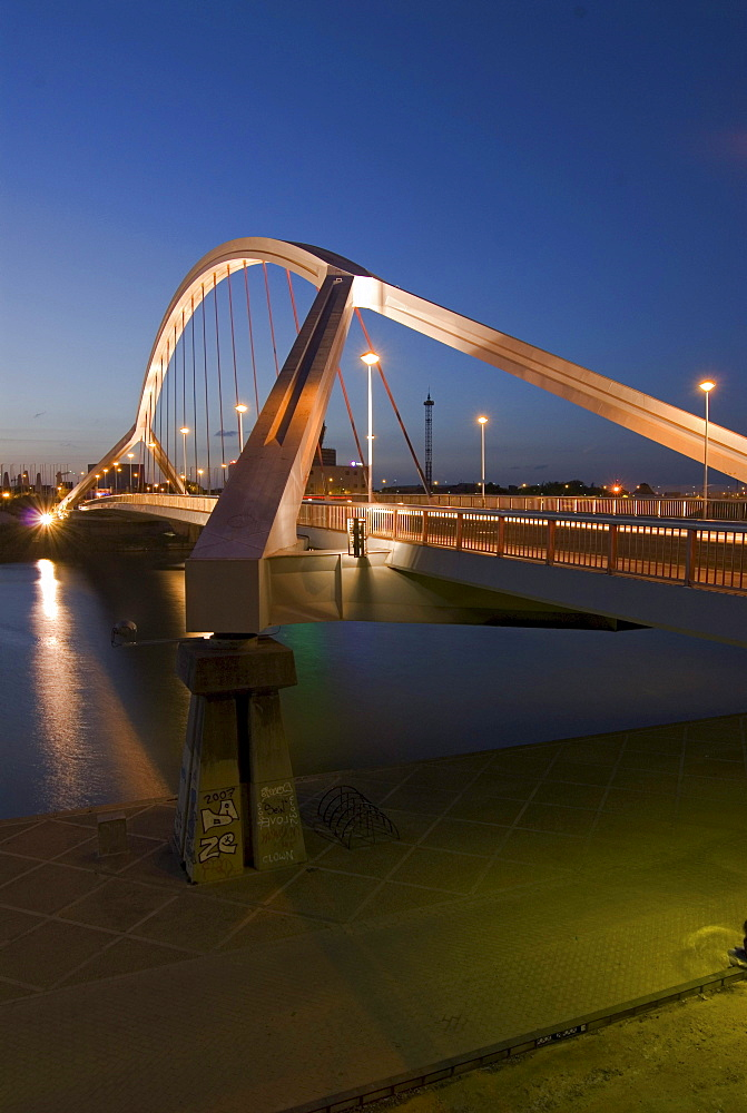 The floodlit Barqueta bridge, Puente de la Barqueta, over Guadalquivir River, at night, constructed to provide access to the Expo 92, Seville, Spain, Europe