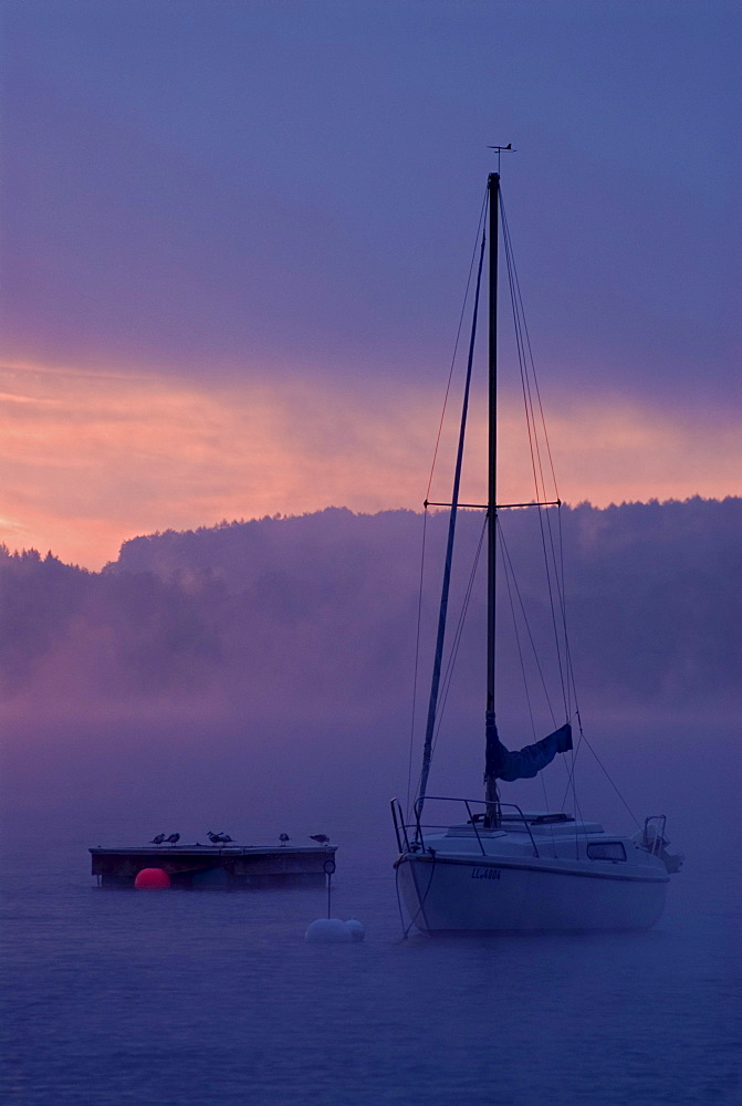 Sun rising behind sailing boats and fog over Ammersee lake, Bavaria, Germany, Europe