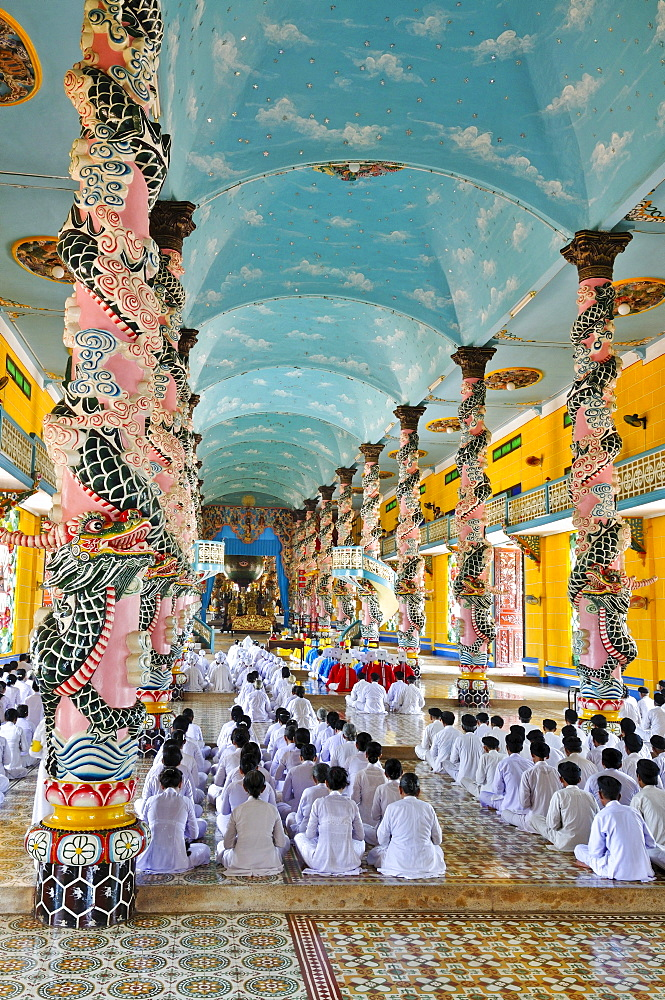 Praying devout men and women, ceremonial midday prayer in the Cao Dai temple, Tay Ninh, Vietnam, Asia