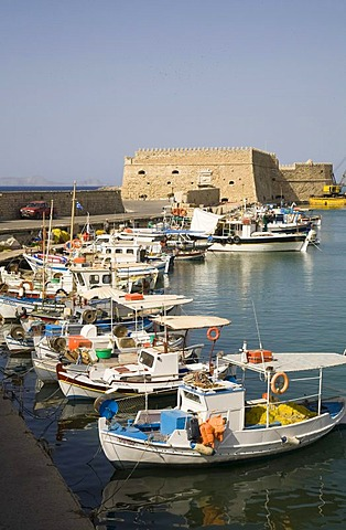 Fishing boats anchoring in the Venetian harbor of Heraklion, behind them the fortress of Kastro Koules in Heraklion, island of Crete, Greece, Europe
