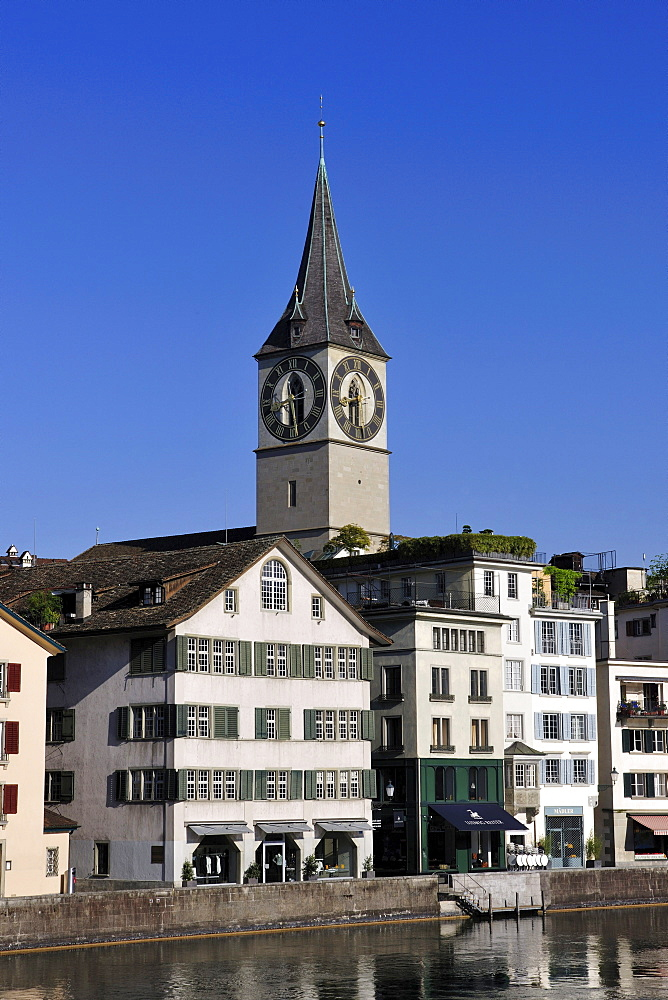 Tower of St. Peter's Church overlooking the rooftops of the historic town centre of Zurich with the Limmat River in the foreground, Zurich, Switzerland, Europe