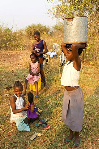 Girl carrying a water jug on her head, African village Sambona, Southern Province, Republic of Zambia, Africa