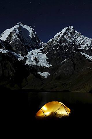 Tent glowing in the dark at Laguna Carhuacocha, Yerupacha, left, and Yerupacha Chico, behind, Cordillera Huayhuash, Peru, South America