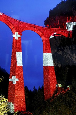 "Irrigation water viaduct lit up with the national flag motif to celebrate the acceptance of the ""Rhaetische Bahn Railway in Albula/Bernina"" as a UNESCO World Heritage Site, Filisur, Graubuenden, Switzerland, Europe"