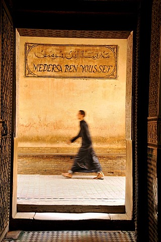 Man wearing a cloak walking through an alley at the Ben Youssef Madrasah, Qur'an school, in the medina quarter of Marrakesh, Morocco, Africa