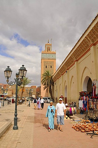 Moroccan couple in front of the tower of the Kasbah Mosque, Marrakesh, Morocco, Africa