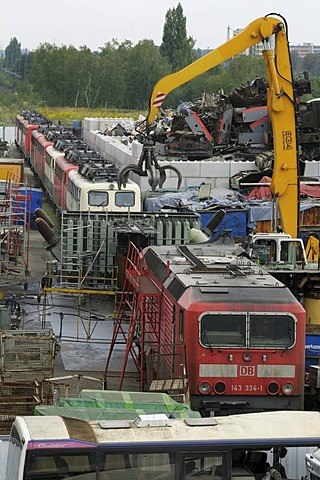 View of scrap yard, recycling yard, 9 E-locomotives, large gripper for junk, utilization of metal