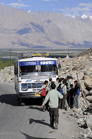 Students wearing uniforms getting on the school bus in Hunder, Nubra Valley, India, the Himalayas