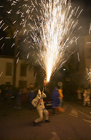 During the Correfoc or fire run, hooded Fire Devils run through the streets of Spanish towns brandishing fireworks, Altea, Costa Blanca, Spain, Europe