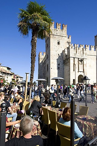 Tourists sitting in a cafe in front of the Scaligero Castle, Sirmione, Lake Garda, Lago di Garda, Lombardy, Italy, Europe