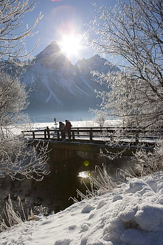 Hikers standing on a snow-covered bridge in front of Sonnenspitze mountain, Tyrol, Austria, Europe
