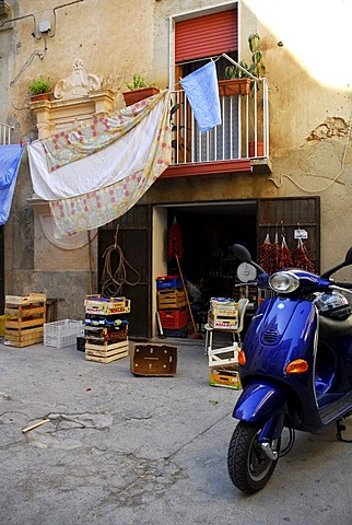 Blue motor scooter, small shop in an inner yard, washing hanging from a balcony, Tropea, Vibo Valentia, Calabria, South Italy, Europe