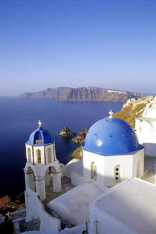 Village of Oia with a church in white and blue, view of the caldera, Island of Thirasia, Therasia in the back, Island of Santorini, Thera or Thira, Cyclades, the Aegean, Mediterranean Sea, Greece, Europe