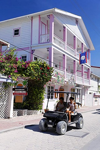 Two women in a golf cart driving past a wooden house painted in Caribbean colors, San Pedro, Ambergris Cay Island, Belize, Central America, Caribbean