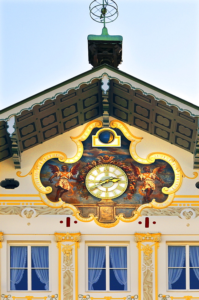 Building facade brightly painted with golden angel motifs surrounding a clock (lueftlmalerei), Bad Toelz, Bavaria, Germany