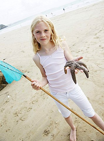 Blonde girl standing on the beach, smiling, holding a fishing net and a starfish
