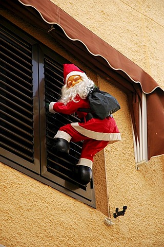 Santa Claus climbs up a window shutter, Polop, Costa Blanca, Spain