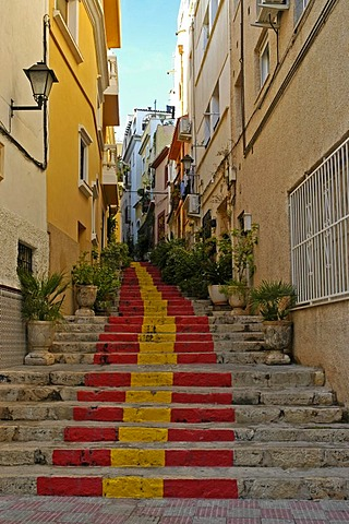 Steep lane with stairway steps in the Spanish national colors, old part of town of Calpe, Costa Blanca, Spain