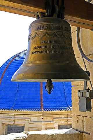 Church bell in the bell tower in front of blue ceramics dome of the baroque basilica from the 17th century, basilica Santa Maria, Elx, Elche, Costa Blanca, Spain