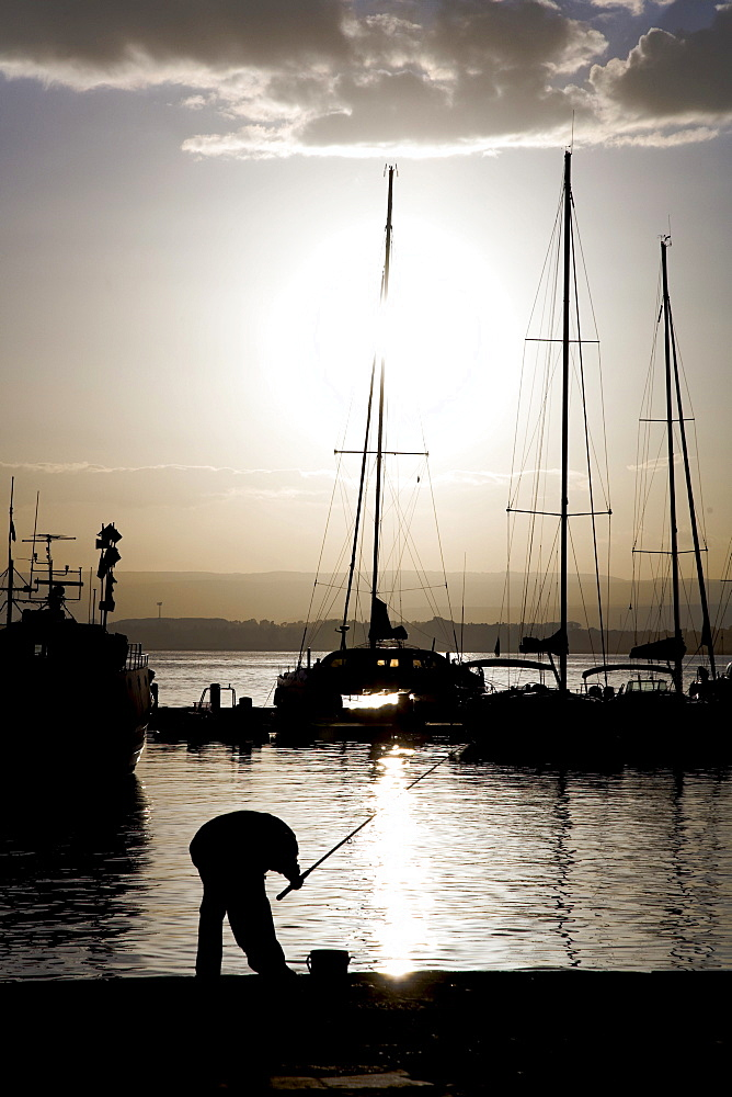 Fisherman silhouetted at the harbour of Syracuse, Sicily, Italy