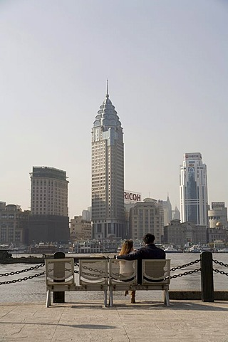 Couple sits on a bench looking at the City, Pudong, Shanghai, China