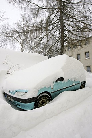 Snowed in car on a snow covered parking lot in Oberwiesenthal, Erzgebirge, Erz Ore Mountains, Saxony, Germany