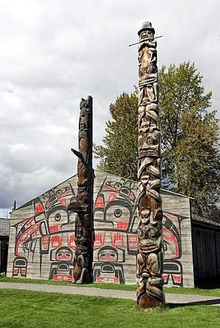 Totem pole in front of long houses at Ksan Historical Village, British Columbia, Canada