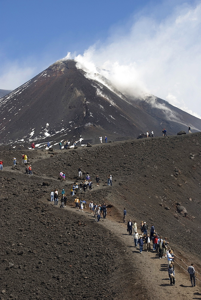 Tourists hiking to Mt. Etna, smoke, Sicily, Italy