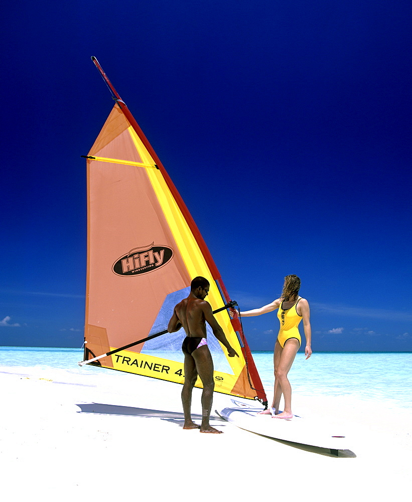 Young woman with a windsurf board, windsurfing lessons, Maldives, Indian Ocean