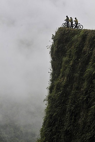 Mountainbikers at the edge of a dangerous cliff, Deathroad, Yungas, La Paz, Bolivia, South America