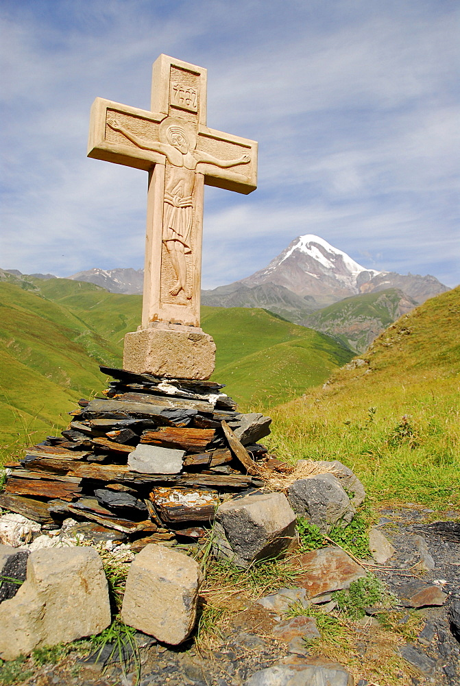 Cross at Gergeti Church in front of 5047 meters high Kasbeg peak, Kasbegi, Georgia