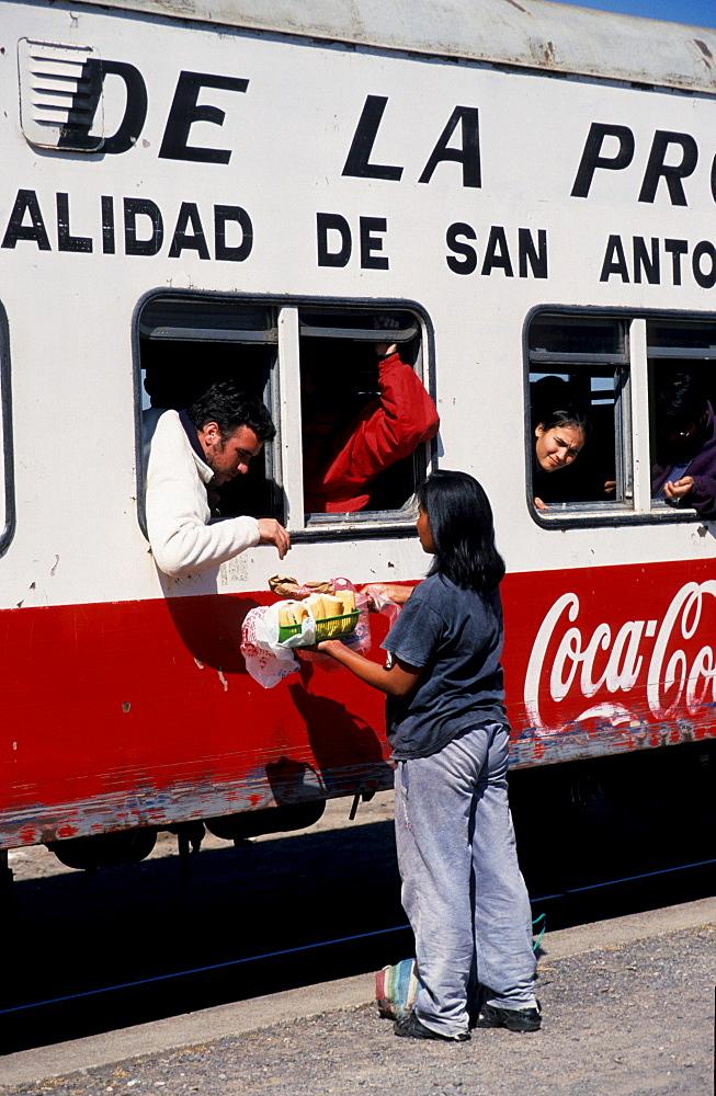 Saleswoman in front of carriage, Tren a las Nubes, Cloud Train car, Salta Province, Argentina