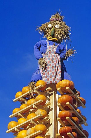 Straw made doll on top of a stack of pumpkins