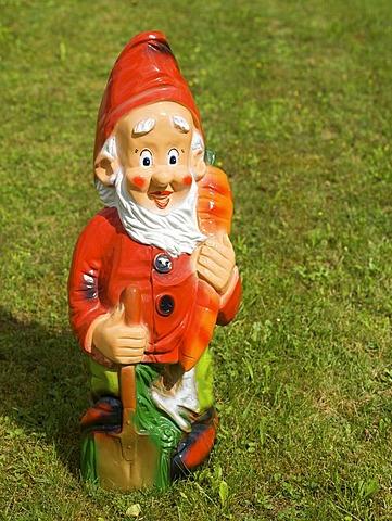 Garden gnome holding a spade and a carrot