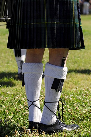 Scottish bagpiper in traditional kilt with a dirk in his woolen socks