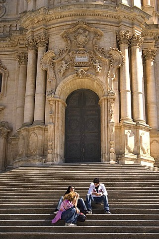 On the stairs in front of the Cathedral of San Giorgio main portal Modica Italy