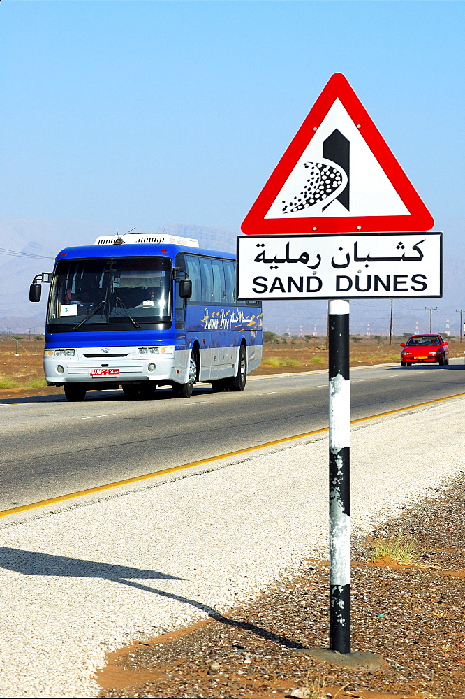 Road sign warning against encroaching sand dunes posted alongside the Wahiba Sands Desert, Ramlat al Wahaybah, Oman, Middle East