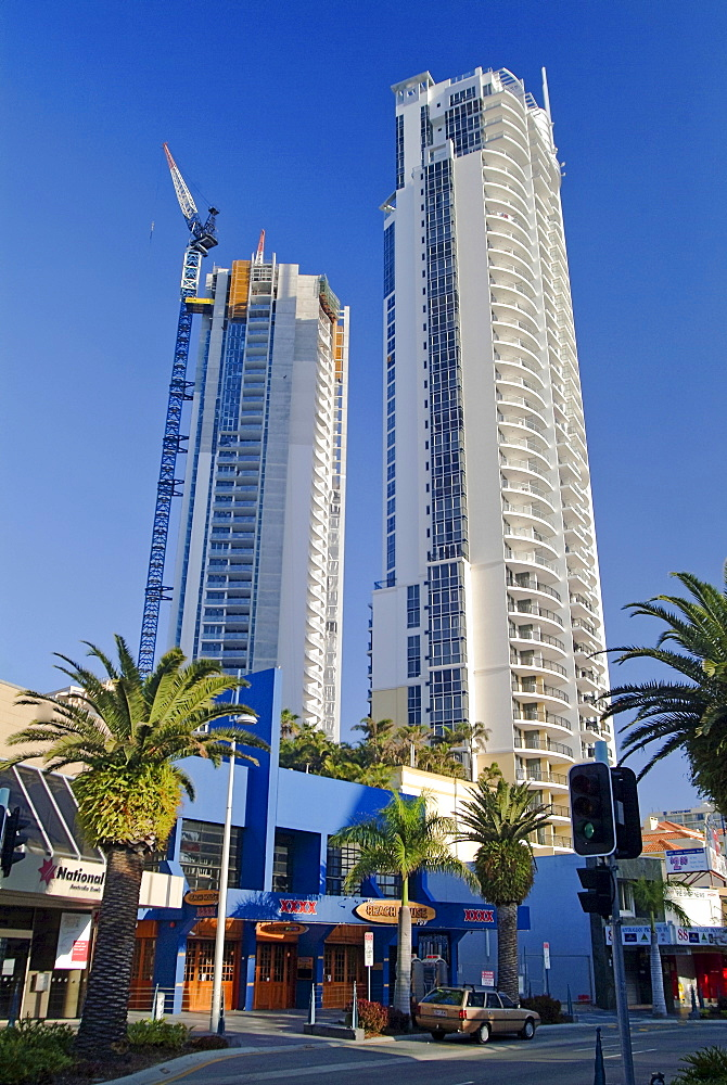 Palm-lined commercial street, high-rises and crane working on the upper stories of a building site, Surfer's Paradise, Queensland, Australia