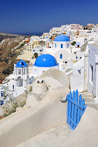 Blue and white domed church and a blue wooden gate in front of interlocked houses in the town of Oia, Ia, Santorini, Cyclades, Greece, Europe